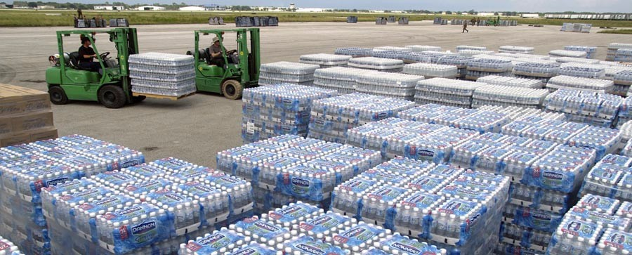 Palettes of bottled water being moved by forklift